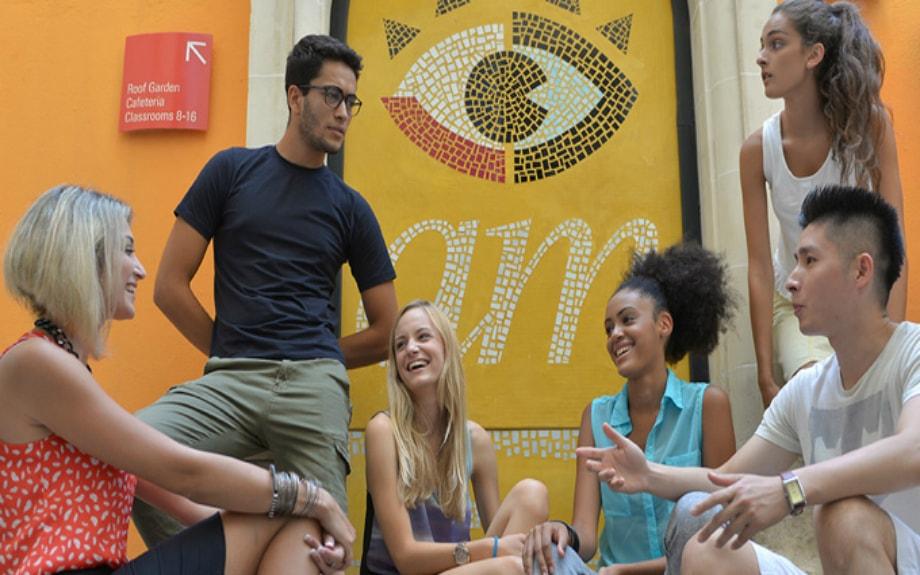 マルタの人気語学学校AM Language Studioのロゴ前で談笑する生徒達