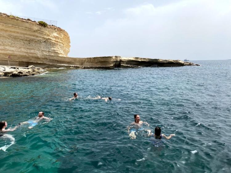 6月のマルタの海で泳ぐ人たち